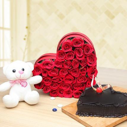 Beautiful roses in box with chocolate cake